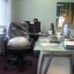 desk and chair covered in saran wrap