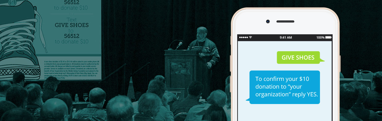 "speaker at podium with call to action on screen with instructions to text keywords ""GIVE SHOES"" to donate. smartphone in foreground with text message donation keywords ""GIVE SHOES"" on screen."