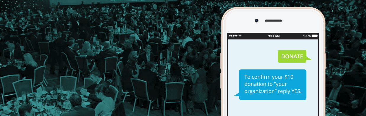 people dining at a charity event with a smartphone in foreground with text message donation.